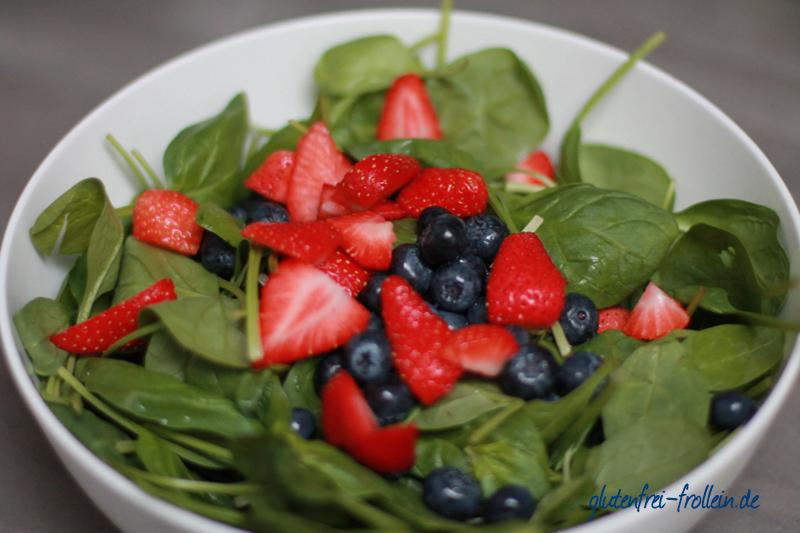 spinatsalat mit frischen beeren in der schuessel